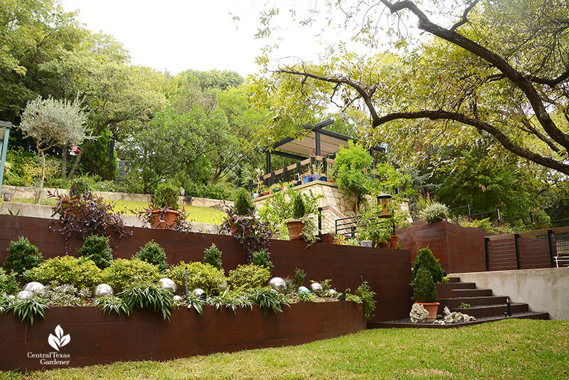 steel planters and retaining wall to upper outdoor living area sloped yard design Dujon Harper