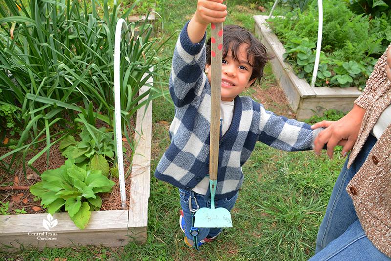 child with hoe La Otra Flora garden